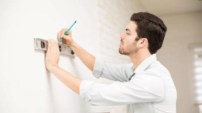 محل قرار گیری حفره های پیچ را با مداد روی دیوار مشخص کنید.